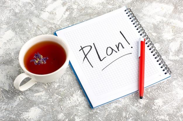 Xícara de chá de vista superior com caderno e lápis na superfície branca