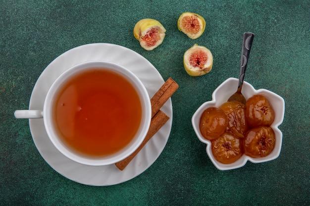 Xícara de chá de vista superior com canela e geléia de figo no fundo verde