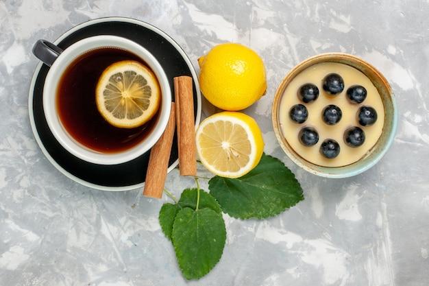 Xícara de chá de vista superior com canela e limão na superfície branca