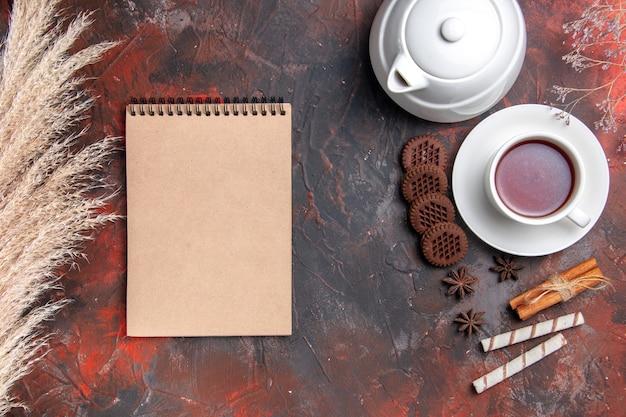 Xícara de chá de vista superior com chaleira e biscoitos no chão escuro, foto de chá escuro