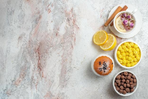 Xícara de chá de vista superior com doces e rodelas de limão em um espaço em branco claro