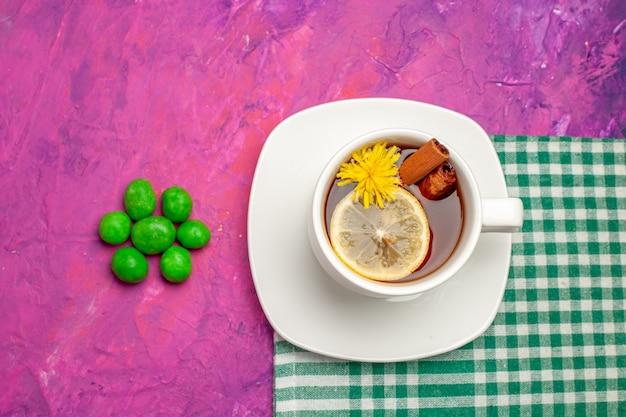 Xícara de chá de vista superior com doces verdes em doces cor de chá de mesa rosa