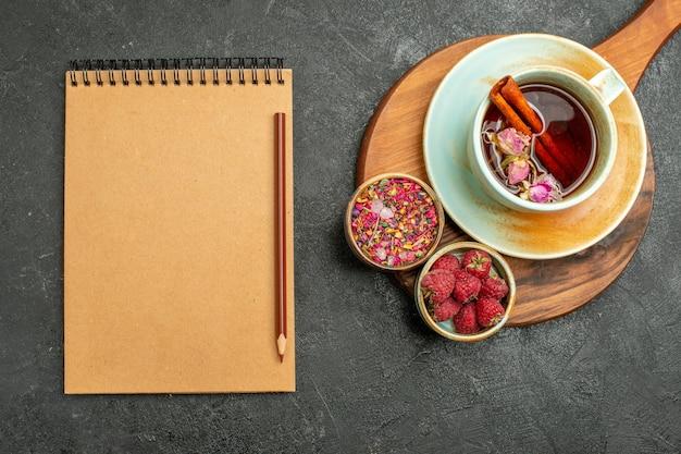 Xícara de chá de vista superior com flores e bloco de notas em fundo cinza flor de cerimônia de cor de bebida