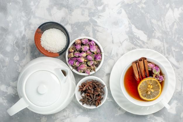 Xícara de chá de vista superior com flores secas e chaleira na superfície branca