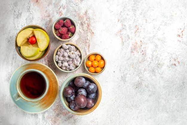 Xícara de chá de vista superior com frutas e doces no fundo branco chá fruta doce fresco