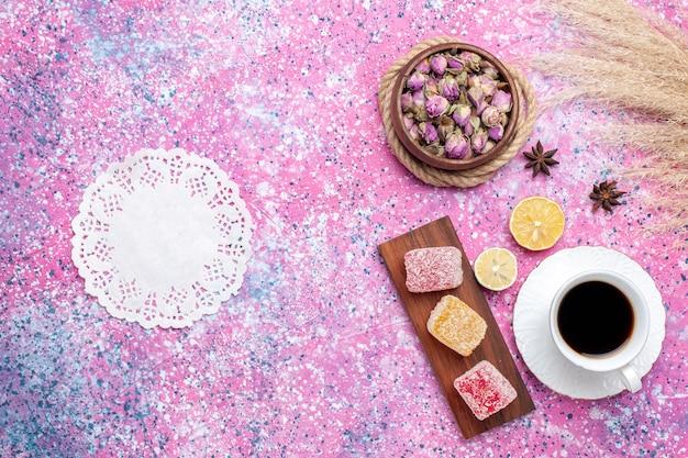 Xícara de chá de vista superior com geleia no fundo rosa.