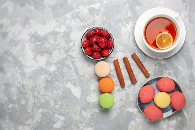 Xícara de chá de vista superior com macarons e bolos em uma superfície branca
