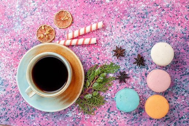 Xícara de chá de vista superior com macarons franceses coloridos na mesa rosa