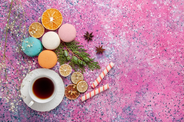 Xícara de chá de vista superior com macarons franceses coloridos na superfície rosa