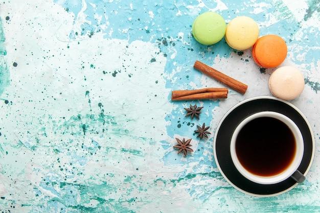 Xícara de chá de vista superior com macarons franceses na superfície azul