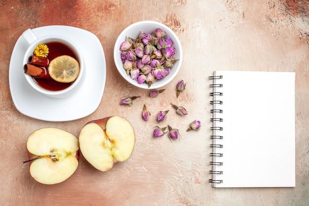Xícara de chá de vista superior com maçãs e flores na flor de chá de frutas de mesa clara