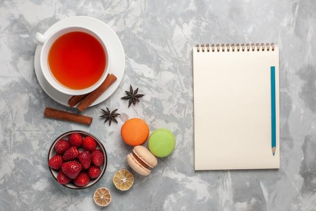 Xícara de chá de vista superior com morangos frescos e macarons franceses na superfície branca