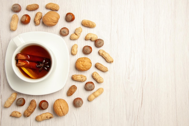 Xícara de chá de vista superior com nozes diferentes na superfície branca, porca, amendoim, chá, lanche, muitos