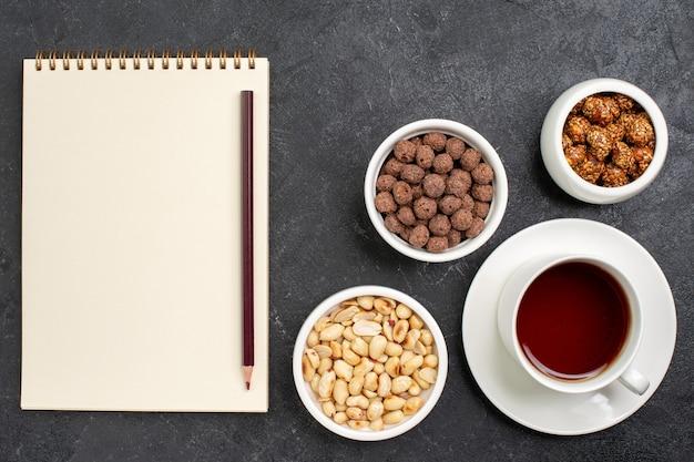 Xícara de chá de vista superior com nozes e doces no espaço cinza escuro