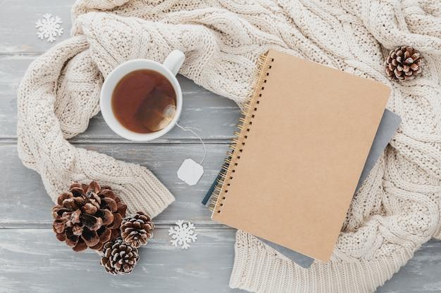 Xícara de chá de vista superior com pinhas e agenda