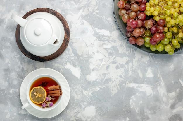 Xícara de chá de vista superior com uvas frescas na superfície branca