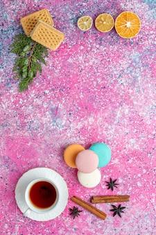 Xícara de chá de vista superior com waffles de macarons franceses e biscoitos na mesa rosa claro