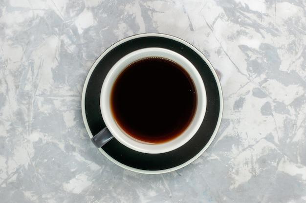 Xícara de chá de vista superior dentro da xícara e prato na superfície branca clara