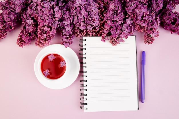 Xícara de chá, diário e buquê lilás