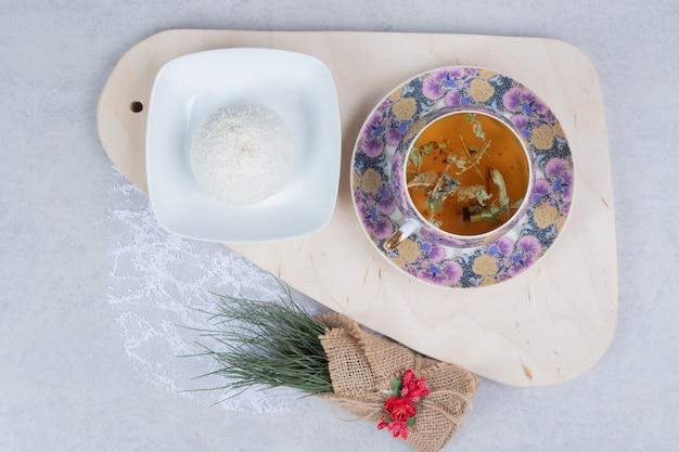 Xícara de chá e biscoito de coco na placa de madeira com decoração de natal. foto de alta qualidade