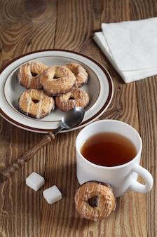 Xícara de chá e biscoitos com chocolate no café da manhã na mesa de madeira