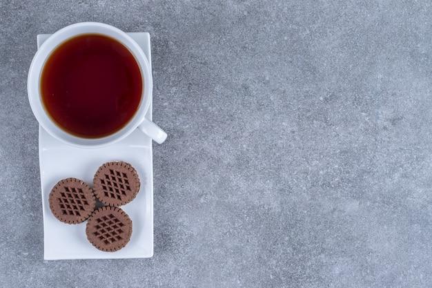 Xícara de chá e biscoitos de cacau em prato branco