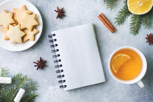 Xícara de chá e biscoitos, galhos de pinheiro, paus de canela, estrelas de anis