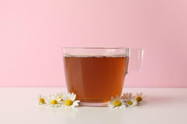 Xícara de chá e camomila na mesa branca contra rosa