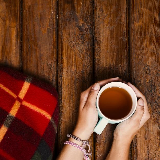 Xícara de chá e cobertor de inverno na madeira velha