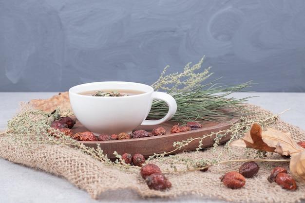 Xícara de chá e cranberries secas na serapilheira. foto de alta qualidade