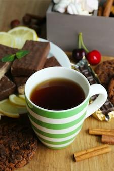 Xícara de chá e doces de perto