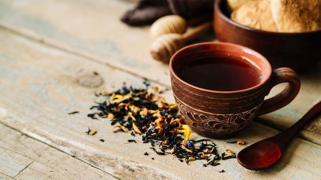 Xícara de chá e ervas no fundo de madeira