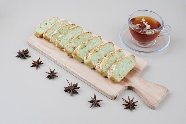 Xícara de chá e fatias de bolo de pistache em branco com cravo.