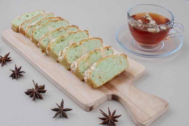 Xícara de chá e fatias de bolo de pistache em branco.