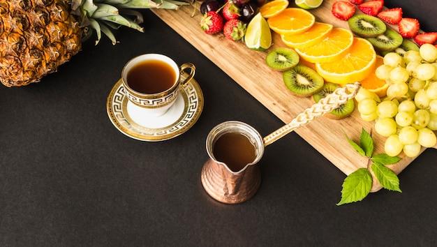 Xícara de chá e fatias de frutas na tábua sobre o fundo preto