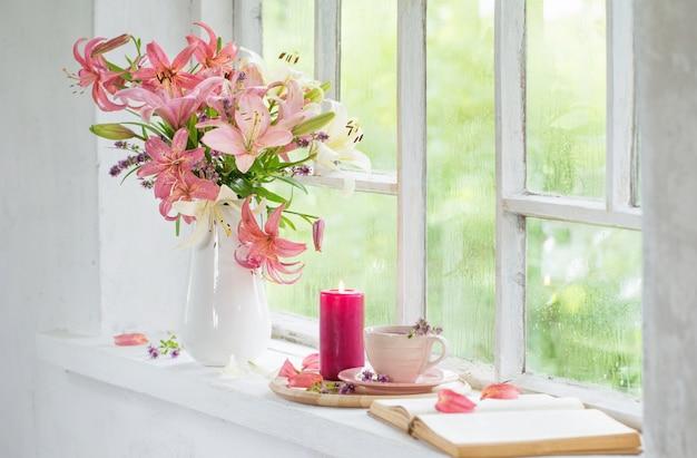 Xícara de chá e flores de verão em janela vintage