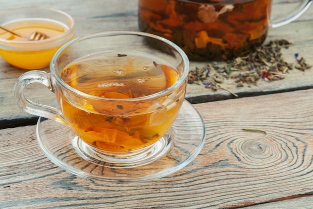 Xícara de chá e folhas de chá na mesa de madeira