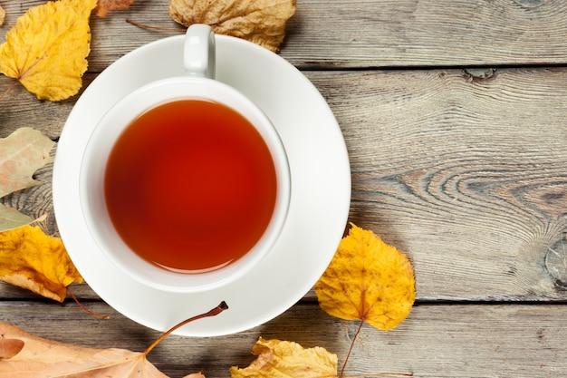 Xícara de chá e folhas de outono em cima da mesa