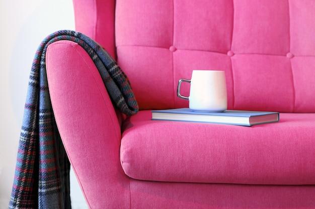 Xícara de chá e livro azul em uma carruagem rosa com um cobertor de perto