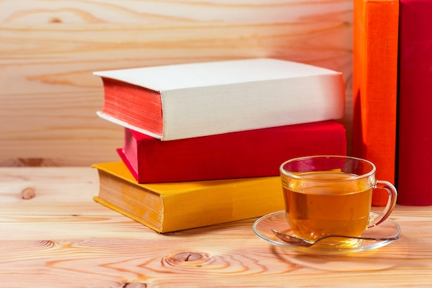 Xícara de chá e livros onwooden fundo
