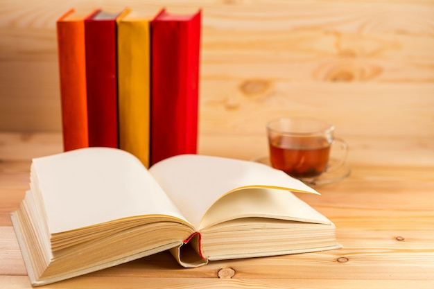 Xícara de chá e livros sobre fundo de madeira