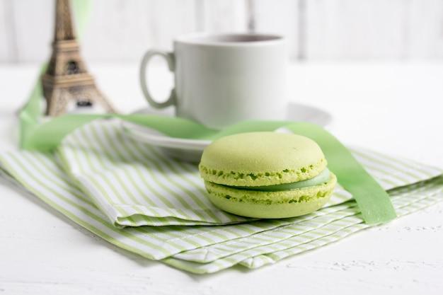 Xícara de chá e macaroons de francês verdes em um branco de madeira