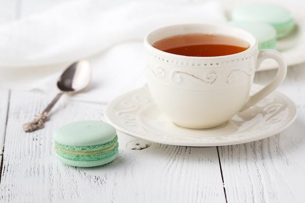 Xícara de chá e macaroons na mesa pastel vintage