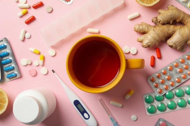 Xícara de chá e medicamentos diferentes em rosa, vista de cima