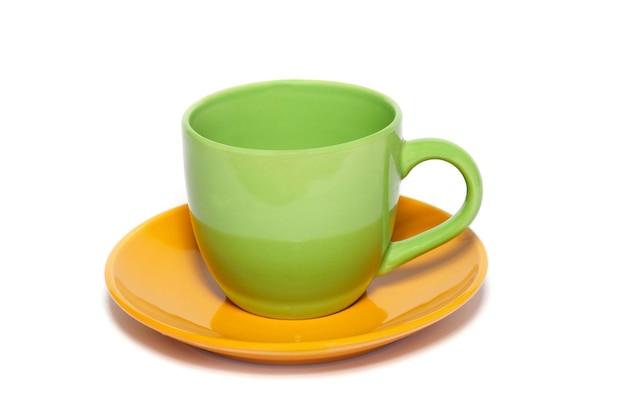 Xícara de chá e pires coloridos isolados no branco.