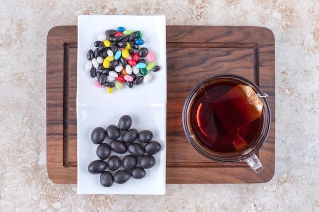 Xícara de chá e prato de chocolates na tábua de madeira