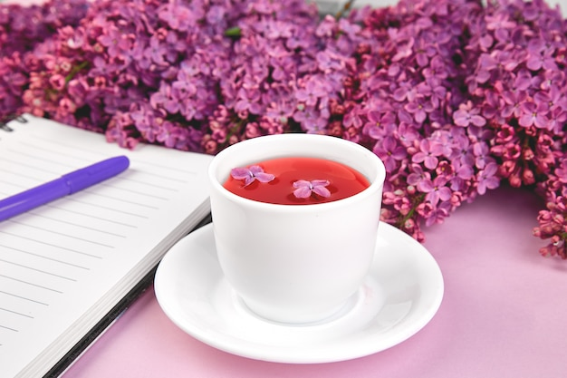 Xícara de chá e ramos de primavera flores buquê lilás florescendo na mesa roxa.