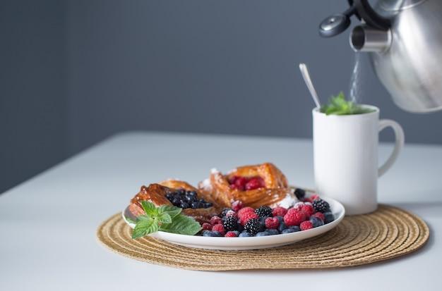 Xícara de chá e sobremesa com frutas vermelhas