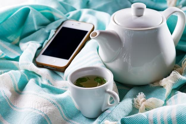 Xícara de chá e telefone celular em uma cama com um bule de chá em uma manta azul