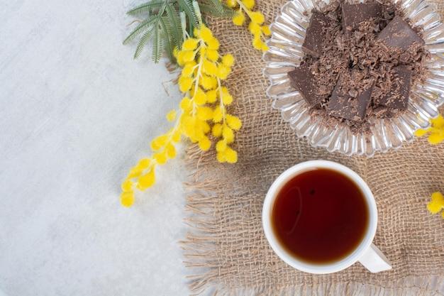 Xícara de chá e tigela de chocolate sobre estopa com flores